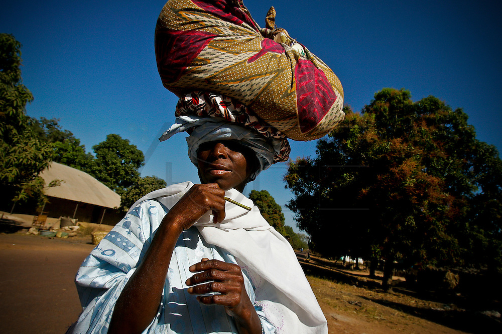 A woman walks by down the road to Farim.