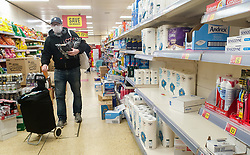 © Licensed to London News Pictures. 05/05/2020. London, UK. A shopper wearing a face covering walks past part empty shelves of toilet rolls despite of high quantities of other stock in Iceland, Haringey in north London during the coronavirus lockdown. Photo credit: Dinendra Haria/LNP