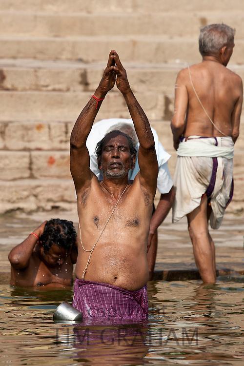 Indian Hindu man bathing and praying in the River Ganges by Kshameshwar Ghat in holy city of Varanasi, India