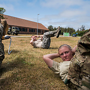 NYMINDEGAB, Denmark -- 6/29/2019 -- U.S. Air Force Tech Sgt. David Bell, center, trains a group of Danish  Home Guard troops in physical fitness as part of the Danish Home Guard Basic Instructor Course. Bell and a small group of U.S. reserve and guard troops participated in the Military Reserve Exchange Program, joining the Danish Home guard for their  summer training session. (U.S. Navy Photo by Chief Mass Communication Specialist Roger S. Duncan)