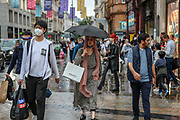 People some of them wearing face protective masks and carrying umbrellas walk near Oxford Circus as it rains in central London on Thursday, Aug 5, 2021. Met Office forecasts 26 hours of heavy rain and thunderstorms to batter the British capital. (VX Photo/ Vudi Xhymshiti)