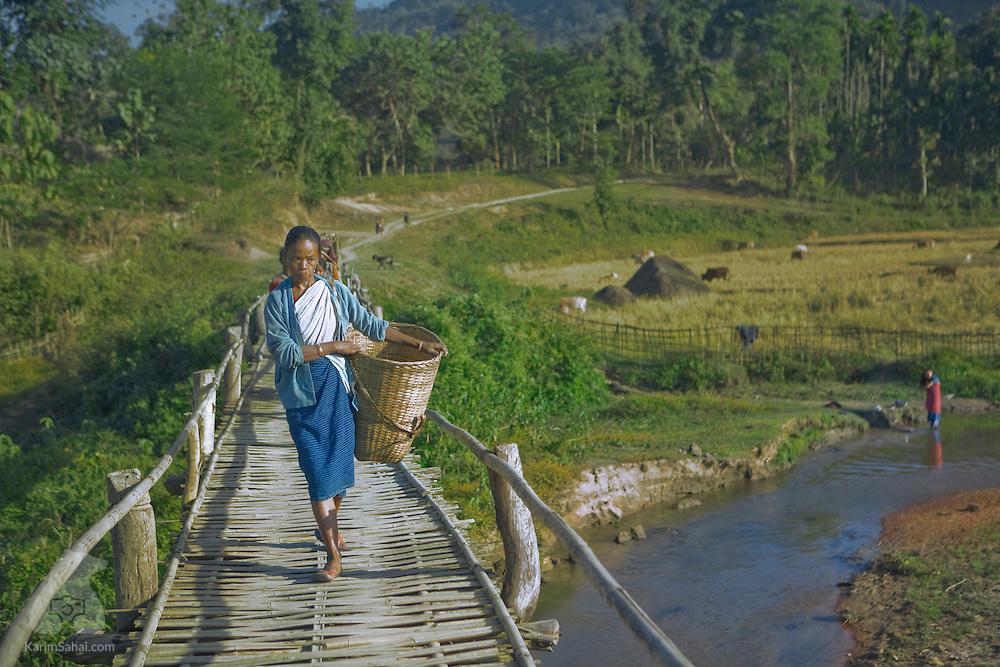 A bodo woman crosses a bamboo bridge, Karbi Anglong District, Assam, India.
