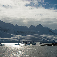 Mountains on Anvers Island rise above the Neumayer Channel near the Antarctic Peninsula, Antarctica. Wiencke Island is in the foreground.
