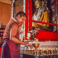 A Tibetan Buddhist monk tends 108 butter lamps at Swaymbhu Temple in Kathmandu, Nepal, 1986.