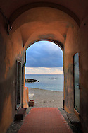 One of the many arches between houses leading directly to the beach of the small town of Varigotti in Liguria, Italy. Taken about 15 minutes before sunset on a cold and windy day of early November.