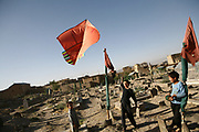 Mohammad Ehsan, 13, center, the eldest son of Noor Agha the kite maker, flies the kite he made himself in the middle of the graveyard near his house, Kabul, Afghanistan, Monday, July, 9, 2007. Noor Agha is a renowned kite maker who made kites for the movie makers of the best-selling novel, The Kite Runner, which will be distributed by Dreamworks and Paramount Vantage in Nov. this year. Noor Agha's wives, using their special glue, help him produce enough kites to please the clients' needs.