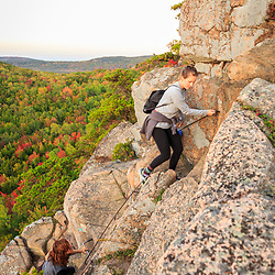 """Hikers climb """"The Beehive"""" in fall in Maine's Acadia National Park."""