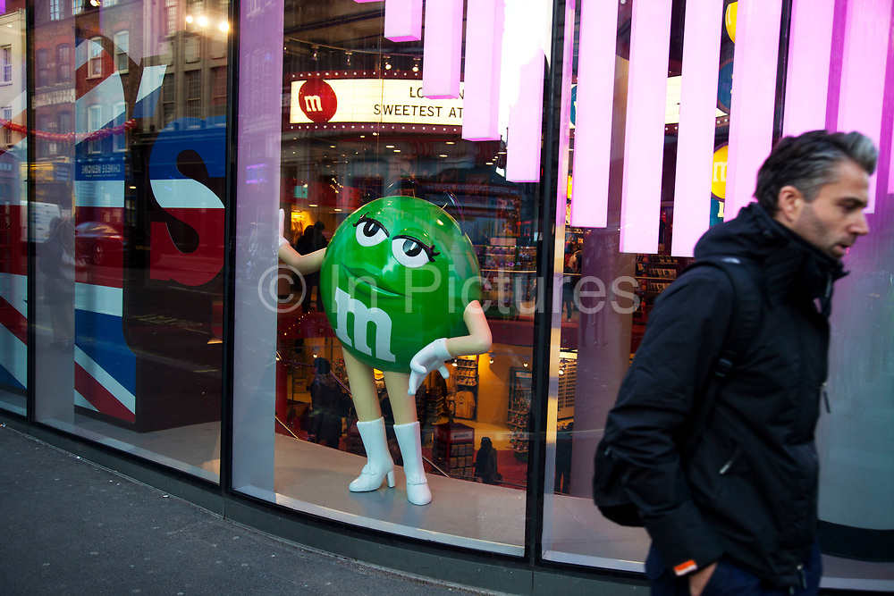 People passing the M&M's themed shop in Leicester Square. Dedicated to the colourful fun of M&M's, the store measures 35,000 square feet and is spread over four floors. It has an extensive range of M&M's chocolates and merchandise. It even has a giant wall of chocolate where you can create your own M&M's selection from over 100 choices.