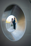 Looking at the bride and groom through a sculpture at the Crocker Art Museum in Sacramento, CA. Wedding photography by Kristina Cilia Photography.