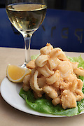 A plate of deep fried Calamari with white wine