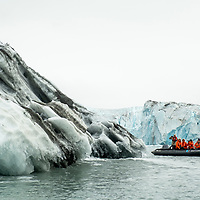 People on an inflatable boat circle a glacial iceberg from the Nordenskjold Glacier in Cumberland East Bay on the north coast of South Georgia Island.