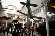 View inside the main atrium at the Imperial War Museum, London. Aircraft from the First and second World Wars are suspended from the ceiling as are various armaments.