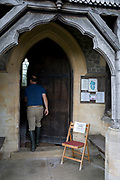 A visitor enters St. Michael and All Angels church where a sign asks people to close the door after them, on 10th September 2018, in Lingen, Herefordshire, England UK.