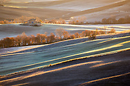 Brushstrokes of light at sunrise caress the slopes of a rural area of the Orcia Valley in the province of Siena in Tuscany, Italy, covered by the morning frost.