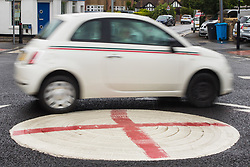 Windsor, UK. 10th July, 2021. A Fiat 500 lined with Italian flag stripes passes a mini-roundabout painted with the St George's flag. The Royal Borough of Windsor and Maidenhead repainted several roundabouts for safety reasons previously daubed with England flags before England's Euro 2020 quarter-final match against Ukraine but it appears that local residents have restored them in advance of the Euro 2020 final between England and Italy.