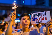 "19 JANUARY 2014 - BANGKOK, THAILAND: A Thai man holds up a candle in Benjasiri Park to pray for peace and support democracy. ""Respect my vote"" has become a rallying cry of people who are concerned their could be a military coup in Thailand. Hundreds of people came to Benjasiri Park, a few hundred meters from the anti-government protest site in Asok Intersection, Sunday evening to pray for peace and rally for a respect for democracy Sunday. The vigil took place a few hours after a two explosive devices, thought to be grenades, were thrown at the protest site near Victory Monument, several kilometers north of Asok. The grenade attack Sunday was the 2nd daytime grenade attack in three days on anti-government protestors. No arrests have been made in the incidents.    PHOTO BY JACK KURTZ"