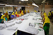 A group of female garment workers folding clothes inside an Epyllion Group garment factory in Bangladesh.