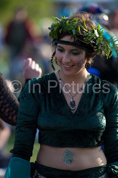 Young woman dressed in Morris dancing attire perform for crowds visitors, english traditions. The annual Beltane celebrations at Butser ancient farm, Hampshire, marking the beginning of the British summer.