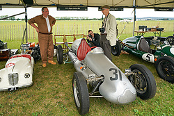 © Licensed to London News Pictures. <br /> 13/09/2019.  <br /> Goodwood.West, Sussex. UK.<br /> The Goodwood Motor Circuit celebrates the 21st year of the Revival.This has become one of the biggest annual historic motorsport events in the world and the only one to be staged entirely in period dress. Each year over 150,000 people descend on this quiet corner of West Sussex to enjoy the three-day event.<br /> Pictured A mechanic talking to motor fans<br /> <br /> Photo credit: Ian Whittaker/LNP