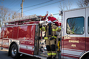19 DECEMBER 2020 - SAYLOR TOWNSHIP, IOWA: SANTA CLAUS, and an a Saylor Township firefighter filling in for an elf, are driven through Saylor Township atop a township firetruck. The Saylor Township Fire Department welcomed Santa Claus to the township on the north edge of Des Moines by showing him around town a fire engine. The event was organized by the Fire Deparment for the town's youngsters who won't be able to see Santa this year because of the Coronavirus pandemic.      PHOTO BY JACK KURTZ