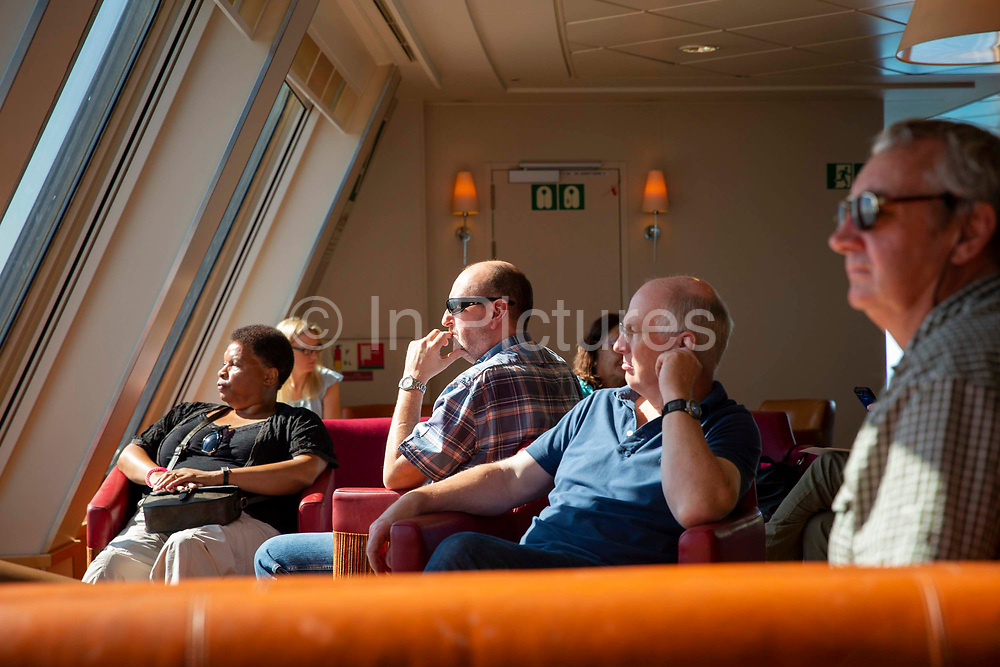 Holidaymakers in the seating area on board a P&O ferry in the English Channel between the Port of Dover and  Calais in France. Dover, Kent, United Kingdom.  Dover is the nearest port to France with just 34 kilometres 21 miles between them. It is one of the busiest ports in the world. As well as freight container ships it is also the main port for P&O and DFDS Seaways ferries.