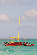 Outrigger canoe with sail in the Pacific Ocean near Oahu, Hawaii.