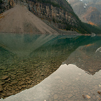 Avalanche debris from Mount Babel reflects in Moraine Lake in Banff National Park, Alberta, Canada. To ther right are Mounts Bowlen, & Tonsa.