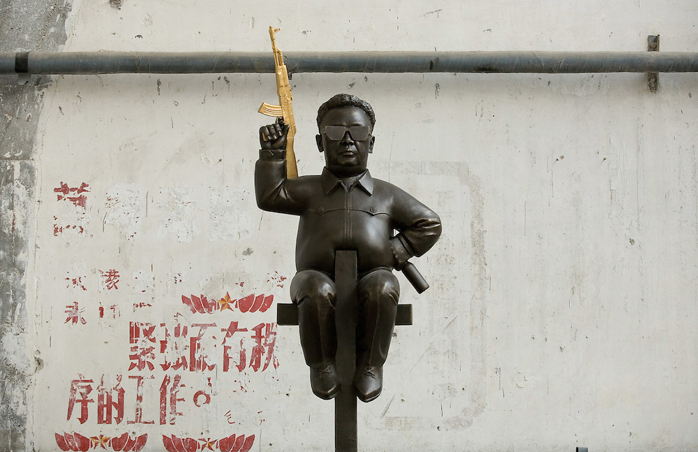 """A sculpture depicts North Korea's """"Dear Leader"""" Kim Jongil with a golden gun, on display at a gallery featuring modern art in Beijing, China May 4, 2007."""