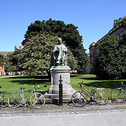 Bikes in the courtyard of Trinity College, Dublin near the statue of William Edward Hartpole Lecky, OM (26 March 1838-22 October 1903), an Irish historian and political theorist. Trinity College (Irish: Coláiste na Tríonóide), formally known as the College of the Holy and Undivided Trinity of Queen Elizabeth near Dublin, is the sole constituent college of the University of Dublin in Ireland. The college was founded in 1592. It is one of the seven ancient universities of Britain and Ireland, as well as Ireland's oldest university. Dublin, Ireland. Photo Tim Clayton