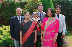 Family group including three generations with women wearing traditional dress,