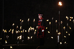 © Licensed to London News Pictures. 04/11/2018. London, UK. A Ueonan Warder stands amongst thousands of flames illuminating the moat of The Tower of London in an installation entitled 'Beyond the Deepening Shadow: The Tower Remembers'. This public act of remembrance for the lives of the fallen, honouring their sacrifice will run for eight nights, leading up to and including the Centenary Armistice Day 2018. The evolving installation will unfold each evening over the course of four hours, with the Tower moat gradually illuminated by individual flames. A specially-commissioned sound installation 'a sonic exploration of the shifting tide of political alliances, friendship, love and loss in war' will be played. At the centre of the sound installation lies a new choral work, with words from war poet Mary Borden's Sonnets to a Soldier. Photo credit: Peter Macdiarmid/LNP