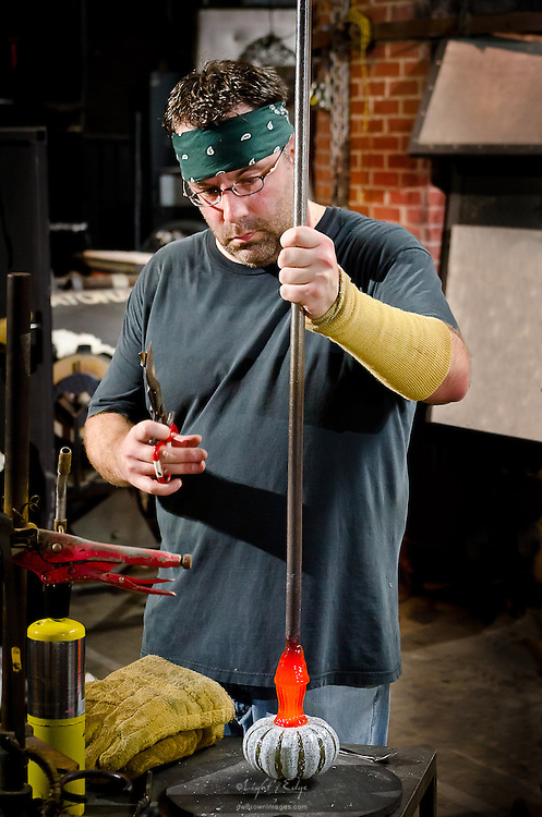 A glass worker in the process of making a glass pumpkin for the 2012 Wheaton Arts Fine Craft Fair.