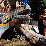 TURISTA JAPONESA EN LA ESCALINATA PRINCIPAL DEL PARQUE GÜELL DECORADA CON UN DRAGÓN DE CERÁMICA, OBRA DEL ARQUITECTO ANTONIO GAUDÍ (1852-1926). BARCELONA. ESPAÑA