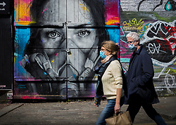 © Licensed to London News Pictures. 23/04/2020. London, UK. A couple wearing face masks pass a mural of a woman wearing a gas mask in Brick Lane, east London. The public have been told they can only leave their homes when absolutely essential, in an attempt to fight the spread of coronavirus COVID-19. Photo credit: Marcin Nowak/LNP