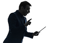 one  business man holding digital tablet surisped shocked in silhouette on white background