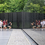 Visitors to the Vietnam War Memorial in Washington DC, with a refleective wall with names of those US soldiers killed in the war.