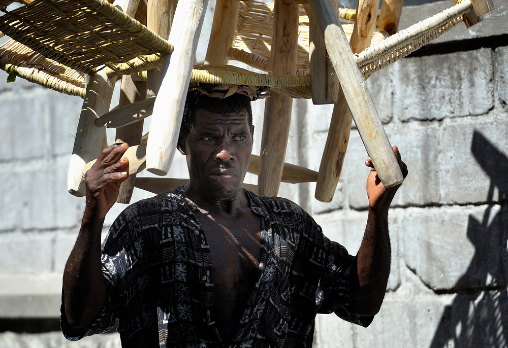 A man carries chairs on his head on a street in Port-au-Prince, Haiti.