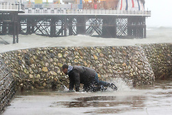 © Licensed to London News Pictures. 26/01/2016. Brighton, UK. A man slips as he gets caught wave on Brighton seafront as the remains of Storm Jonas reach the UK from the USA. Photo credit: Hugo Michiels/LNP
