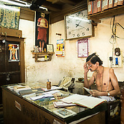 Wearing no shirt, a religious clerk struggles over the temple's expenses. Venkateshwara temple.