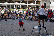 With many people and families staying in the UK for their Summer break during the school holidays, a large number of domestic tourists, who may normally have been travelling abroad, have decended on the capital to see the sights, as seen here in Covent Garden where people have gathered to watch the street performers in the Plaza on 10th August 2021 in London, United Kingdom. Following the Coronavirus / Covid-19 health scare of the last two years, and with some travel restrictions still in place, more people have chosen a staycation which is a holiday spent in ones home country rather than abroad, or one spent at home and involving day trips to local attractions.