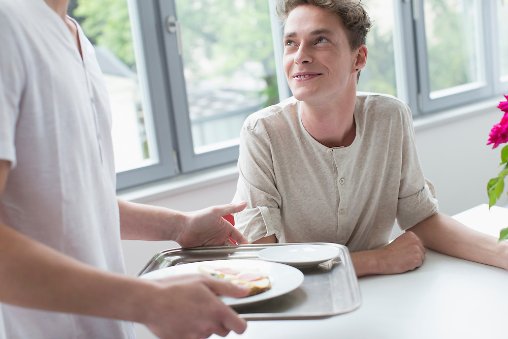 Young man with dinner tray talking to his friend, smiling