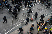 Police personnel drag barricades away as they advance toward protesters near the Central Government Offices, during a protest against a proposed extradition law in Hong Kong, SAR China, on Wednesday, June 12, 2019. Hong Kong's legislative chief postponed the debate on legislation that would allow extraditions to China after thousands of protesters converged outside the chamber demanding the government to withdraw the bill. Photo by Suzanne Lee/PANOS