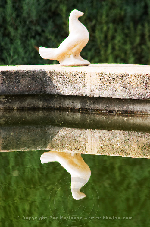 A small statuette of a dove reflected in the garden pond.  Chateau de Beaucastel, Domaines Perrin, Courthézon Courthezon Vaucluse France Europe