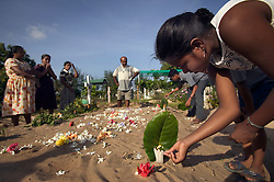 Jennifer Teevanandam, 13, lights a candle for her mother, who she lost in the tsunami, Batticaloa, Sri Lanka, March 7, 2005. Her mother is buried with several other family members killed in the tsunami. The family hopes to build a small monument at the gravesite when they have more money. Residents of the small Christian village Dutch Bar spent more than six weeks in a makeshift refugee camp at the local convent recovering from the devastating tsunami that hit the eastern and southern borders of Sri Lanka. They were then moved into another temporary living camp, while awaiting the building of new homes. More than 150 Residents in this community of less than 1000 people died in the tragic event.