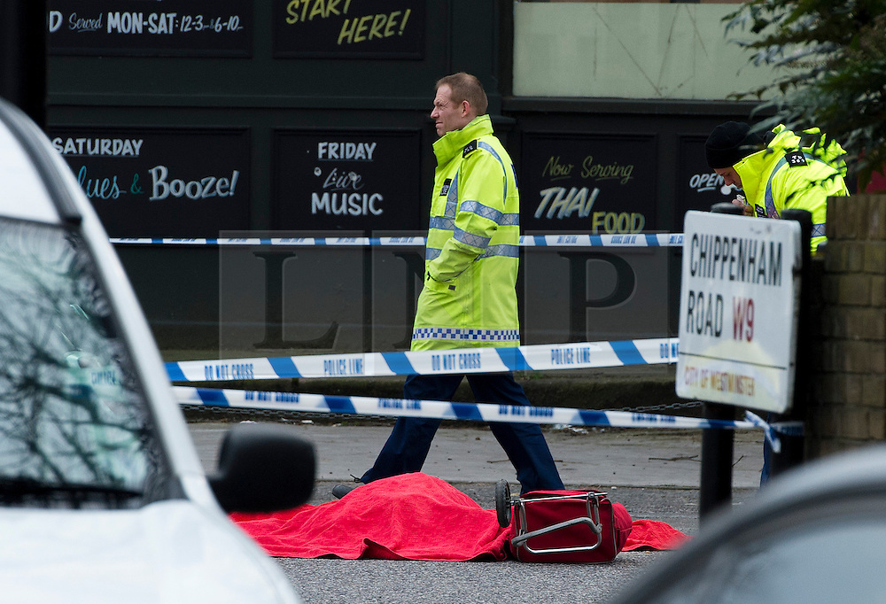 © London News Pictures. 27/03/2013 . London, UK.   Police stand over the body of a woman killed in a collision with a lorry on the corner of Chippenham Road and Harrow Road in London, on March 27, 2013. A red trolley can be seen next to the body. Photo credit : Ben Cawthra/LNP