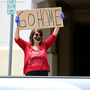 A stay at home supporter argues with protesters at a rally to end the stay at home order and open businesses and schools at Lake Eola on Saturday April 25, 2020 in Orlando, Florida.  Governor Ron DeSantis signed an executive order that restricts non-essential employees and businesses from opening and working. (Alex Menendez via AP)