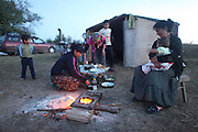 Living in tents, prepared early evening meal. Pachouve family of woodcutters, living in temporary shelters in the hills above Debelets. They cut wood for fuel for several months of the year then go home to Sliven. Bulgaria..Roma Gypsies left India 1000 years ago. Often nomadic. A collection of tribes with their own languages and culture, pushed by the Ottoman empire towards Europe, used and sold as mercenaries, slaves, prostitutes. They endured 500 years of slavery until mid 19th century. A million were killed in the holocaust. Hundreds of thousands exiled and refugees from kosovo. Many Eastern Europe Roma come to the west seeking a better life. They are shunned, marginalized, excluded. Both indigenous and foriegn Roma, whether European citizens or not, lack the opportunities of others, living on the periphery, in the brunt of racism, often deported back to their countries of origin.
