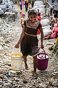 Meera, a young woman living in the slum, carrying buckets filled with water back to her home, Tangra slum, Dhipi, Kolkata, India