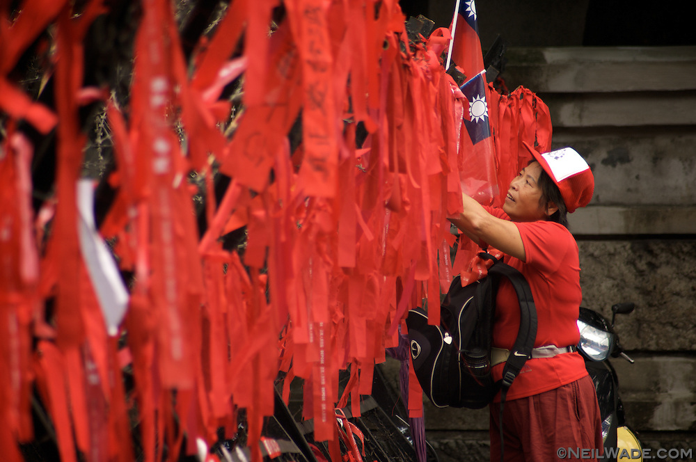 A woman hangs Taiwanese flags at a political protest to depose President Chen in 2006 in Taipei, Taiwan.