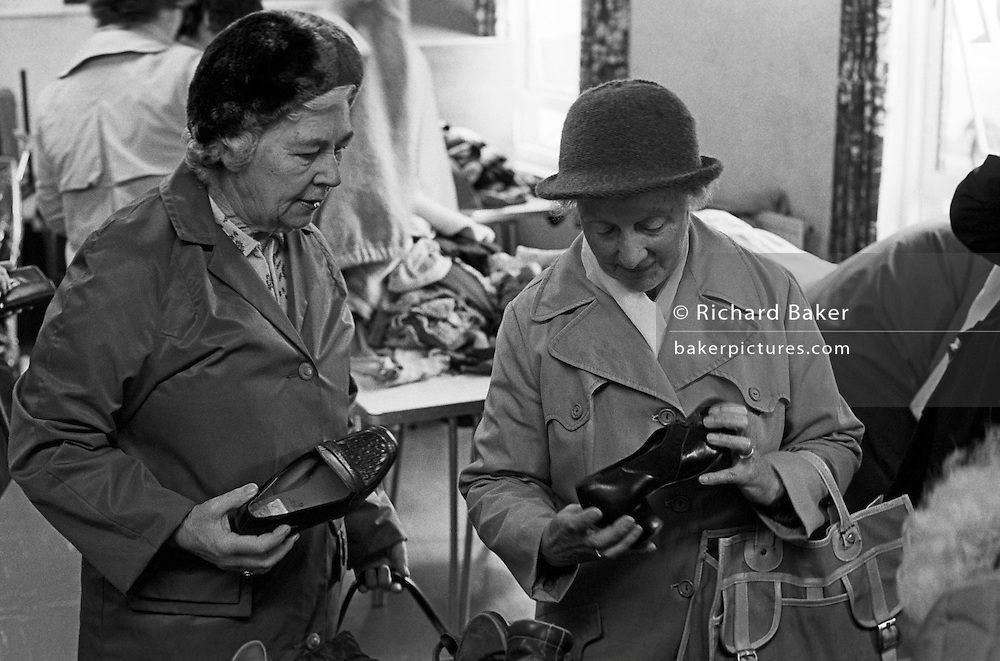 Looking as if from a past era, two ladies examine shoes at a 1986 jumble sale in the south Wales town of Abergavenney, Monmouthshire. Both are holding right-foot shoes that might suit them at this charity event held by the local Lions club, whose volunteers help the elderly and the disadvantaged within their community. We see some of the clothing piled up on trestle tables but the ladies' attention is just on their finds which are within their price range, having to survive on meagre pensions.